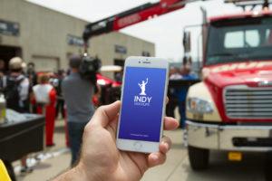 Мокап iPhone в руке на фоне автотрека. iphone at a car race mockup bundle